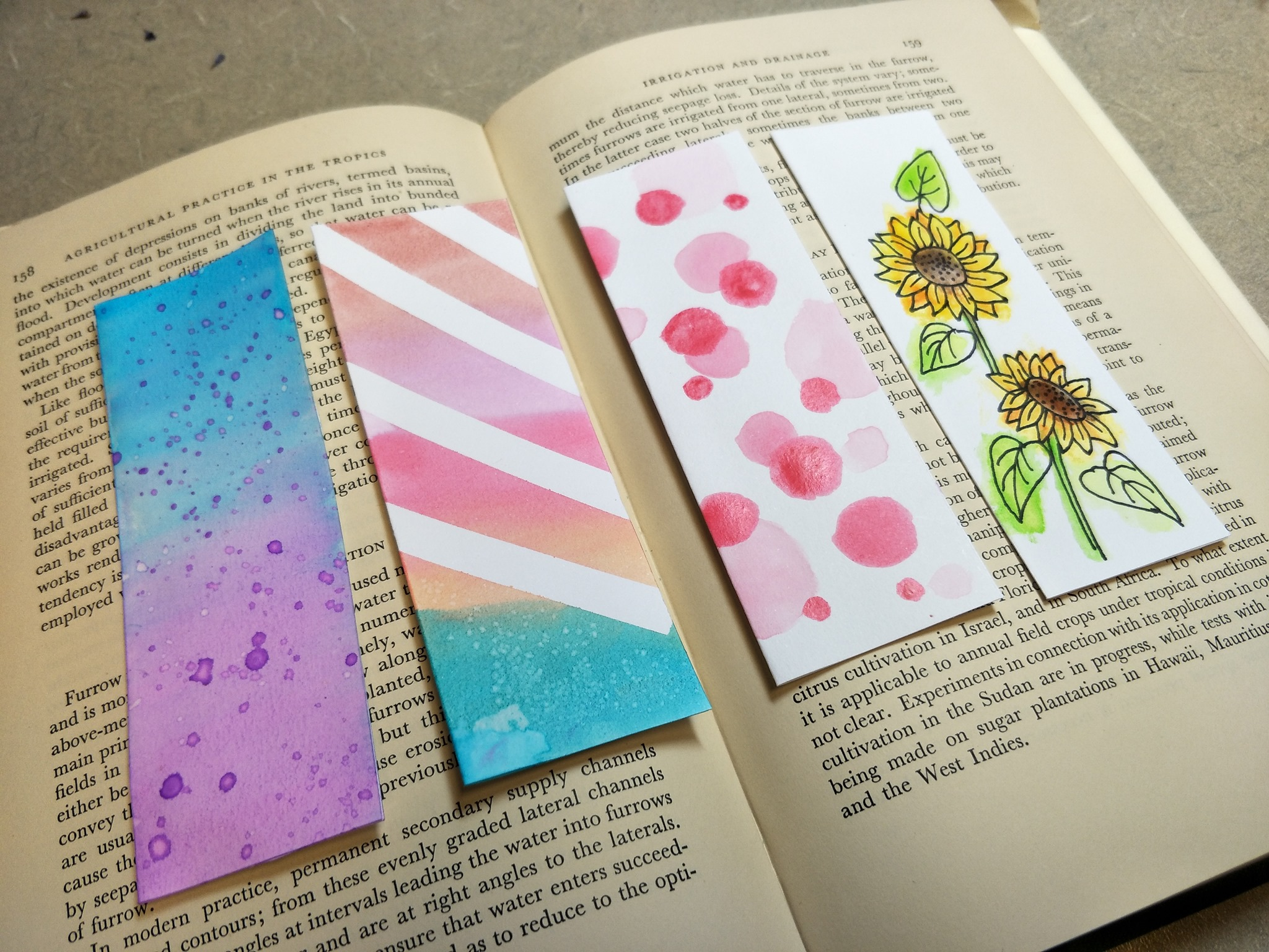 An open book with 4 paper book marks on it. One is purple and blue, one has white stripes, one has red and pink dots, and the other has yellow sunflowers
