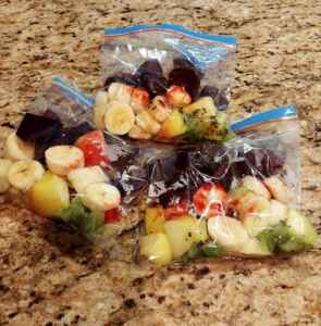 3 small plastic bags with chopped fruit inside, including beets, kiwi, apple, and banana