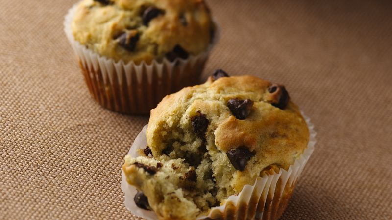 2 Banana chocolate chip muffins sit on a brown table. The muffin closest to the camera has a piece taken out of it